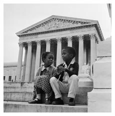 Two children sit in front of the Supreme Court